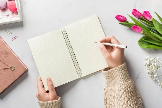 Hand die in leeg notitieboekje schrijft