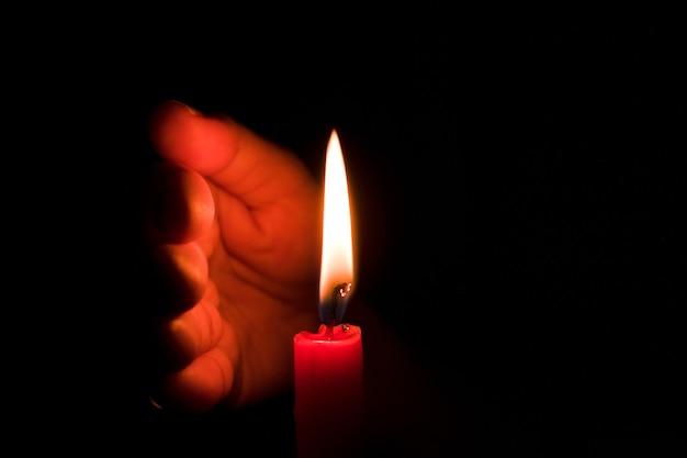 Hand die kaarslicht beschermt tegen de wind in het donker op zwarte achtergrond
