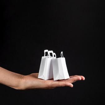 Hand die kleine witte zakken houdt