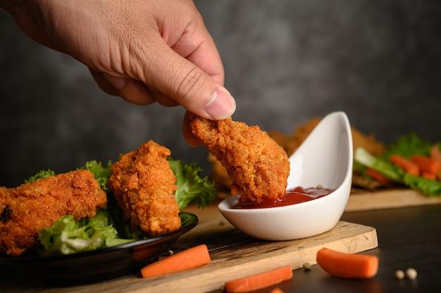 Hand die knapperige gebraden kip houdt die in tomatensaus wordt ondergedompeld