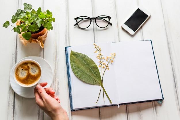 Hand die koffie op creatieve werkplaats neemt