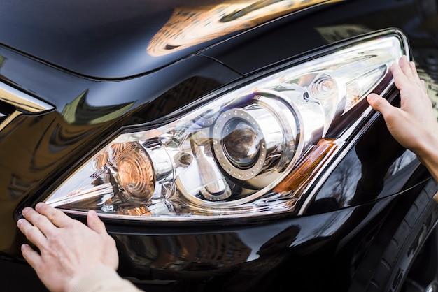Hand die koplamp van zwarte auto houdt