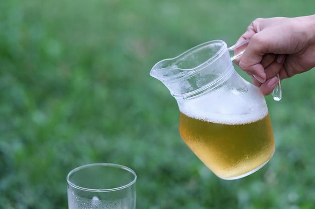 Hand die koud bier voor het drinken in ontspannende tijd houdt