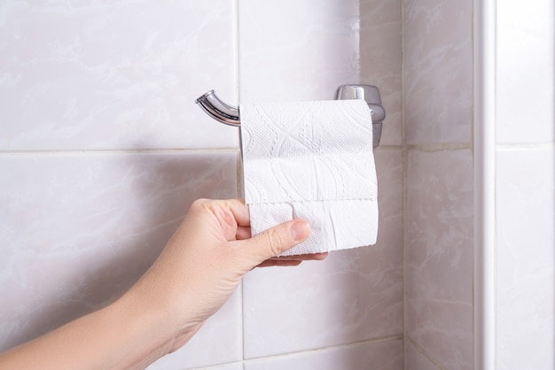 Hand die laatste blad van toiletpapier neemt