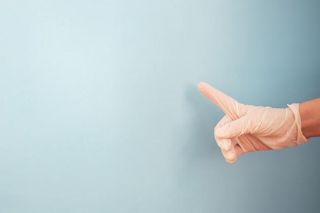 Hand die latexhandschoen met nummer één wijsvinger op blauwe achtergrond draagt. kopieer ruimte.