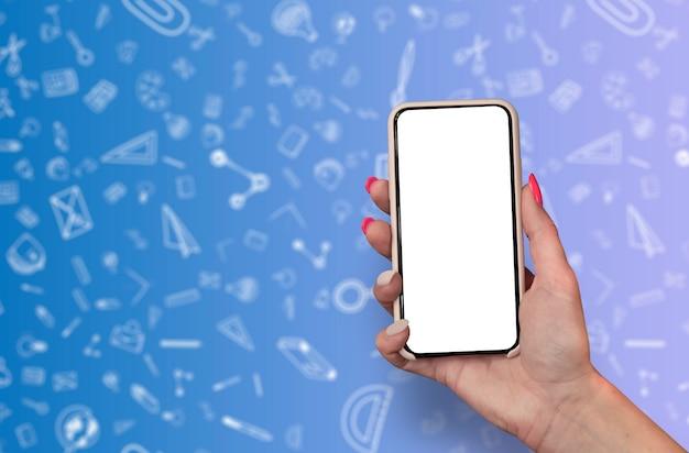 Hand die lege smartphone op de krabbelsachtergrond van de kantoorbehoeftenschool houden