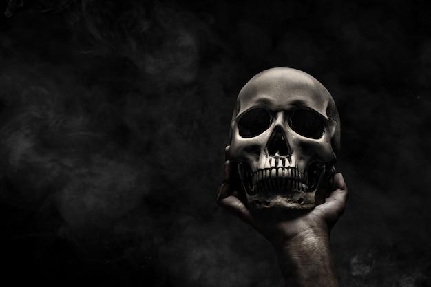 Hand die menselijke schedel houdt