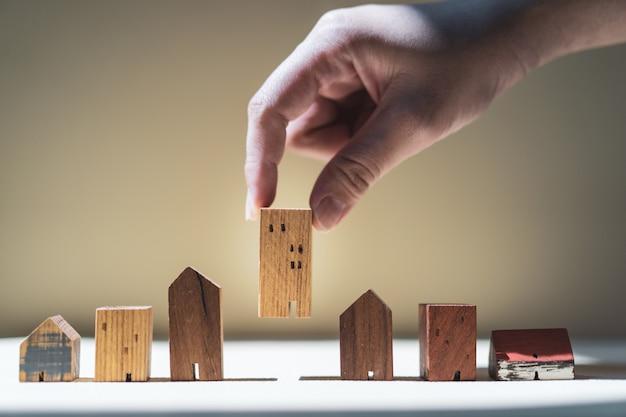 Hand die mini houten huismodel kiezen van model en rij van muntstukgeld op houten lijst