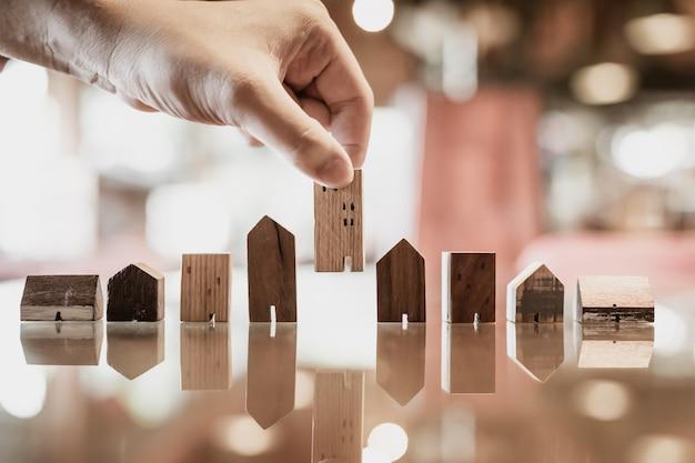 Hand die mini houten huismodel van model op houten lijst kiest