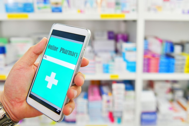 Hand die mobiele slimme telefoon voor zoekbalk houden op vertoning op de achtergrond van drogisterijplanken online medisch.