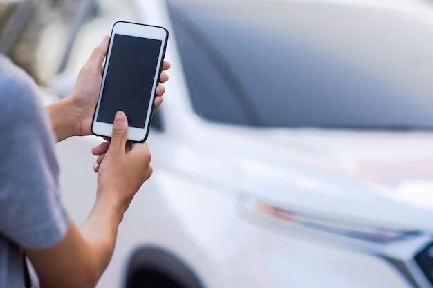 Hand die mobiele slimme telefoontoepassing houden om het slimme leven 5g van de autotechnologie te beginnen