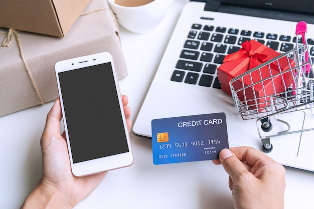 Hand die mobiele telefoon en creditcard met boodschappenwagentje, pakketdozen, laptop op de desktopmening, exemplaarruimte, online het winkelen concept houden.