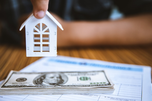 Hand die modelwit huis op dollarbankbiljet houdt. verzekering en vastgoedbeleggingen onroerend goed concept.