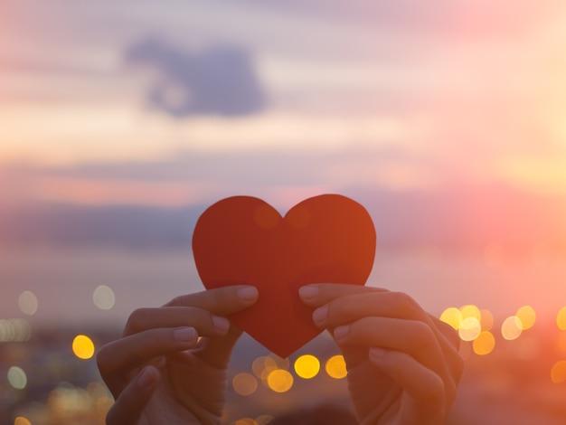 Hand die mooi hart houdt tijdens zonsondergangachtergrond.