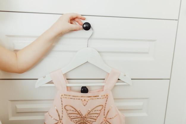Hand die mooie opgedirkte weelderige roze kleding voor meisjes op hanger houden bij de achtergrond van garderobe