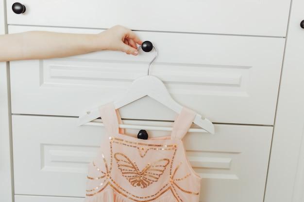 Hand die mooie weelderige roze kleding voor meisjes op hanger houden bij de achtergrond