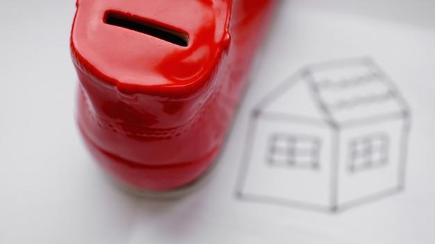 Hand die munt in de spaarpot laat vallen. een huis tekenen op een wit laken in de buurt met een doos