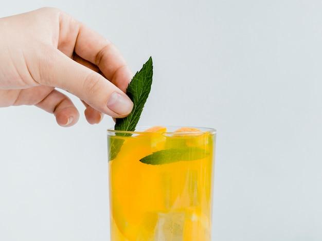 Hand die munt in heldere koude smakelijke drank zet