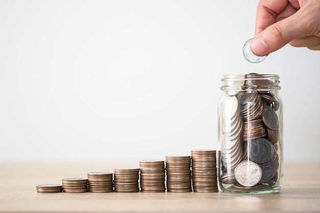 Hand die muntstuk zet aan het bewaren van kruik en het stapelen van muntstukken. geldbesparende investeringswinst en dividendenconcept.