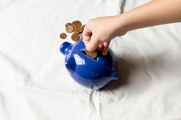 Hand die muntstukken in een spaarvarken zet