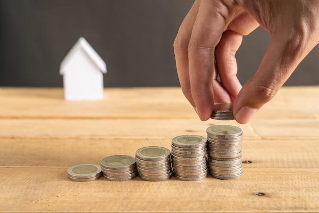 Hand die muntstukken op zwarte houten lijst stapelt met onduidelijk beeld van mini wit huismodel. zaken, financiën, bankwezen en onroerend goed groeien en groeien