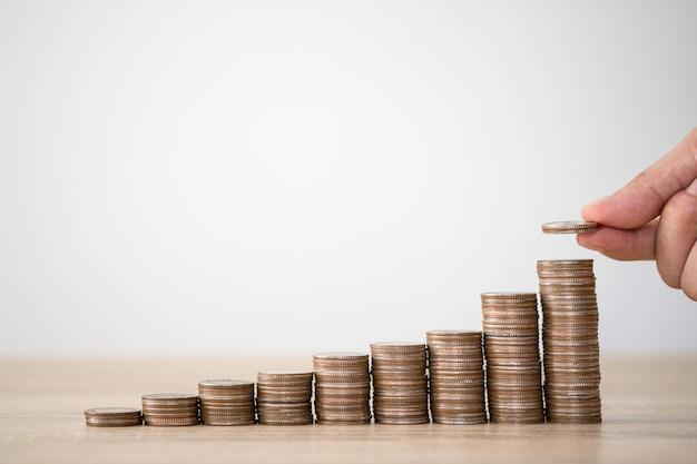 Hand die muntstukken zetten aan het stapelen voor geldbesparende winst en het concept van de bedrijfsinvesteringengroei.