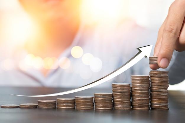 Hand die muntstukken zetten die met stijgende pijl stapelen. dividend van bankstorting en het concept van de voorraadinvestering.
