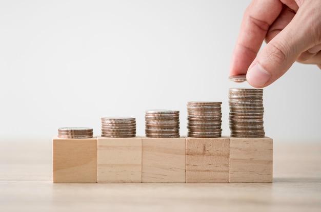 Hand die muntstukken zetten die op houten blok stapelen. investeringen en bedrijfsgroei concept.