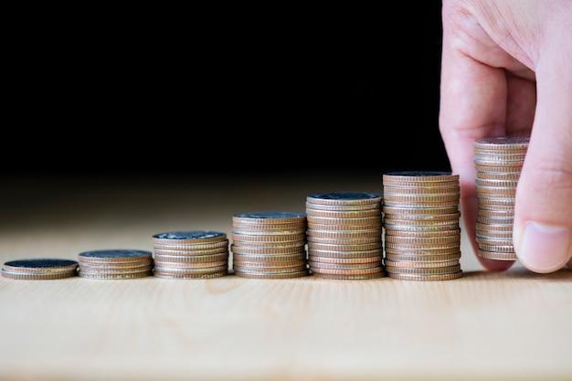 Hand die muntstukken zetten die op zwarte achtergrond stapelen die het symbool is voor het opslaan in de toekomst en de investering van de voorraadwaarde financieren.