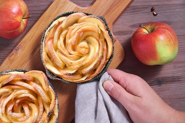 Hand die omemade bladerdeeg met roze gevormde appelplakken houdt die in ijzerkoekepan worden gebakken