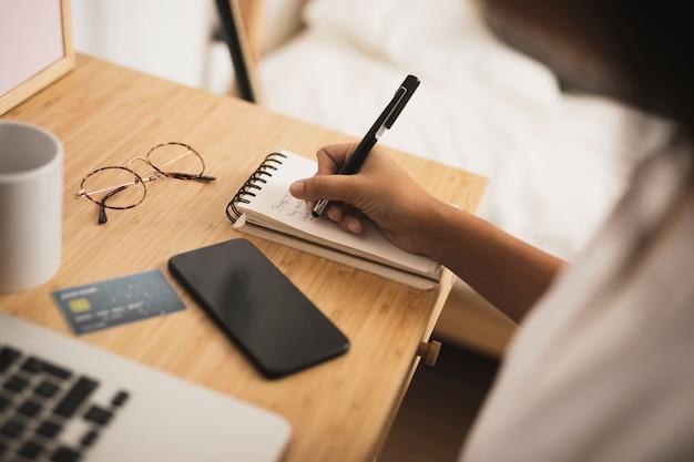Hand die op bureauspot omhoog schrijft