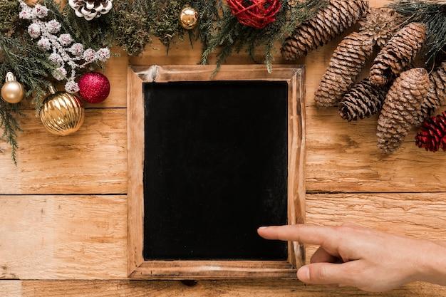 Hand die op fotokader dichtbij naaldtakjes, winkelhaken en kerstmisballen toont