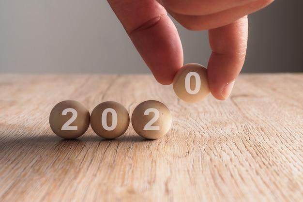 Hand die op het woord van 2020 zet dat in houten kubus wordt geschreven
