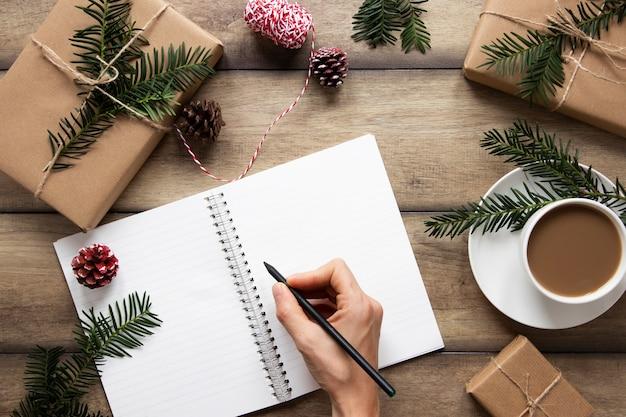 Hand die op notitieboekje dichtbij hete drank schrijft