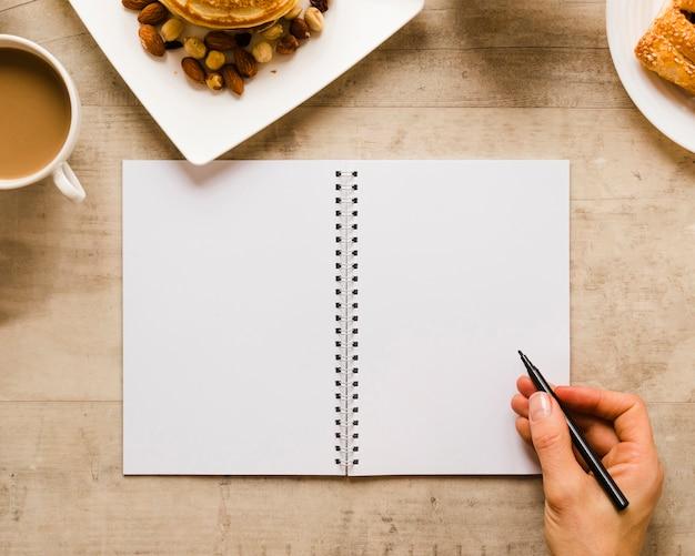 Hand die op notitieboekje met koffie schrijft