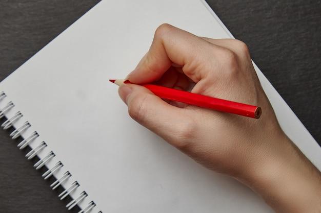 Hand die op notitieboekje met potlood schrijft