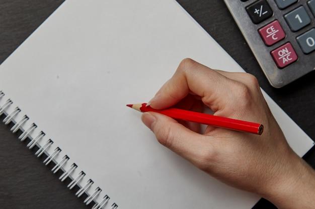 Hand die op notitieboekje met rood potlood schrijft