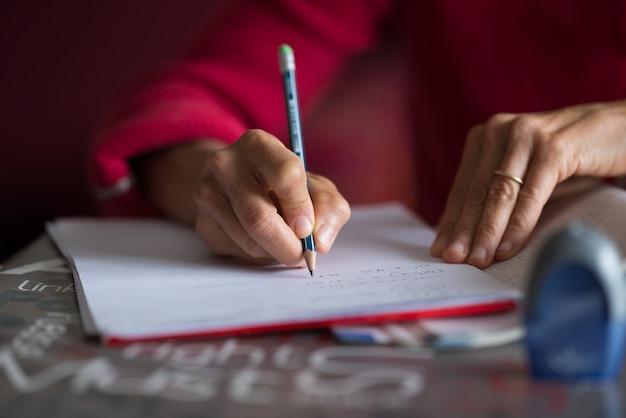 Hand die op papier met potlood op bureau schrijft. selectieve focus op potlood, interieur, zeer ondiepe scherptediepte.