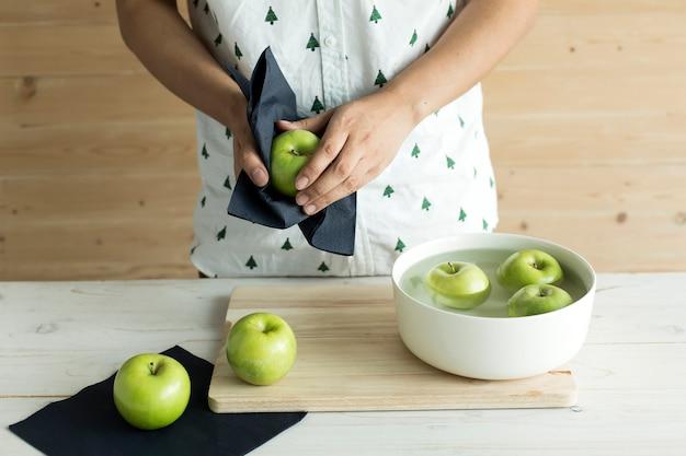 Hand die organische groene appel schoonmaakt