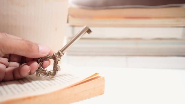 Hand die oude sleutel houdt geplaatst dichtbij de rand van het boek, heeft exemplaarruimte, conceptensleutel van onderwijssucces.