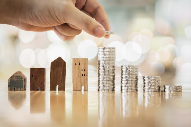 Hand die rij van muntstukgeld op houten lijst en mini houten huis kiest,