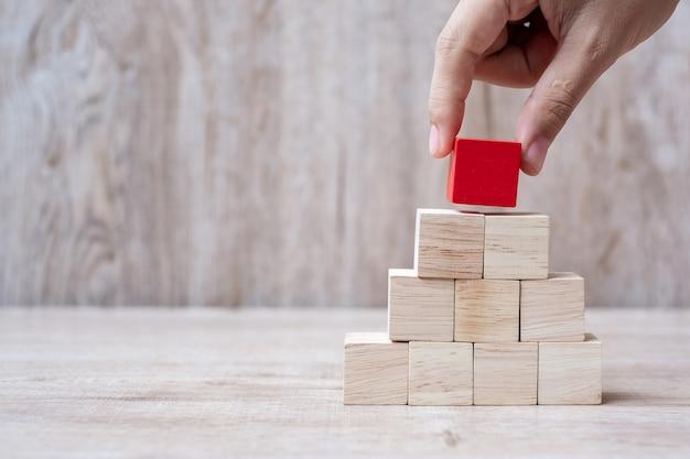 Hand die rood houten blok bovenop plaatst