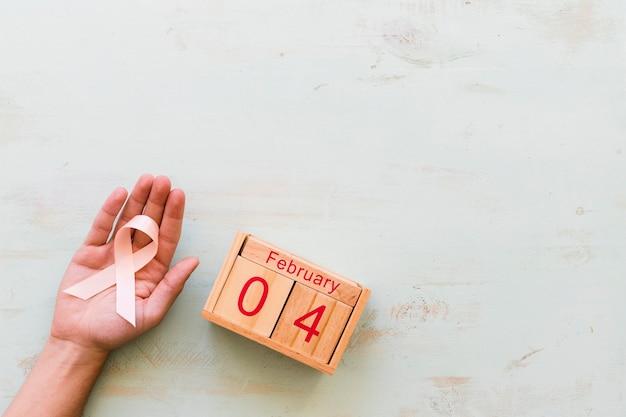 Hand die roze voorlichtingslint en de houten doos van 4 februari op achtergrond houdt
