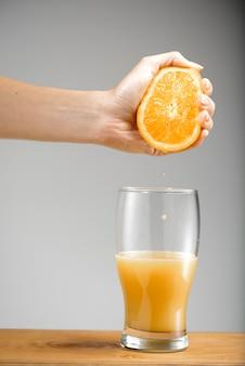 Hand die sap van sinaasappel in glas uitknijpt