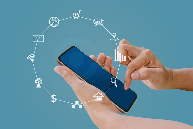 Hand die slimme telefoon met vage sociale media en technologiepictogrammen op blauwe kleurenachtergrond houdt.