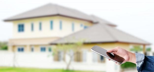 Hand die slimme telefoon over onduidelijk beeldhuis met behulp van, het slimme concept van de huiscontrole