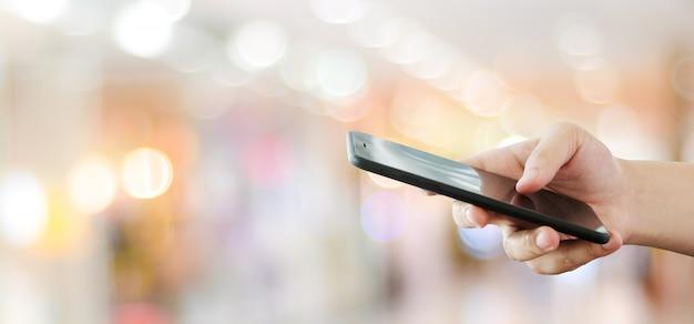 Hand die smartphone gebruiken over onduidelijk beeld bokeh lichte achtergrond