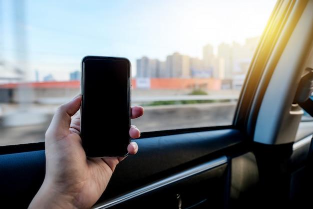 Hand die smartphone grijpen om mobiele toepassing op achterbank van taxiauto te gebruiken.