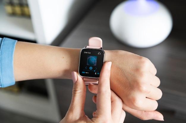 Hand die smartwatch gebruikt voor het afspelen van muziek