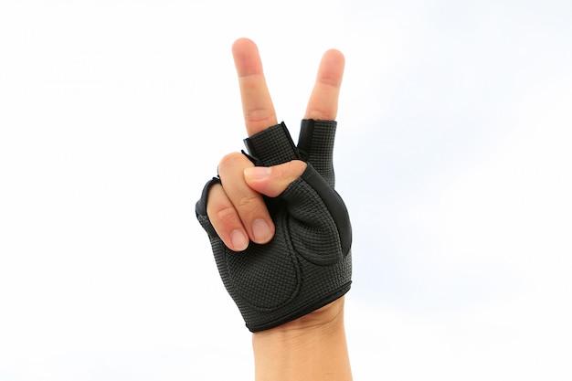 Hand die sporthandschoen draagt die overwinningsteken toont dat op witte achtergrond wordt geïsoleerd.